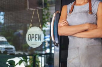 The woman is a waitress in an apron, the owner of the cafe stands at the door with a sign Open waiting for customers. Small business concept, cafes and restaurants